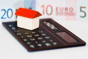 kleines Holzhaus auf Taschenrechner mit Geld im Hintergrund