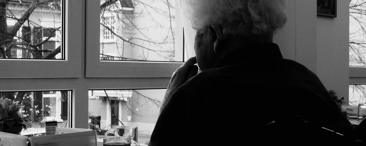 Seniorin sitzt gedankenverloren am Fenster