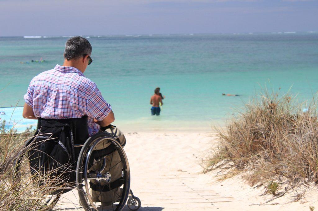 Mann im Rollstuhl am Sandstrand