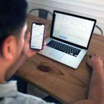 Ein Mann sitzt vor dem Laptop und schaut sich Forex-Währungskurse an.
